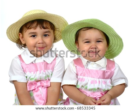 Cute girls in spring Easter dresses, two and three years, Hispanic - stock photo