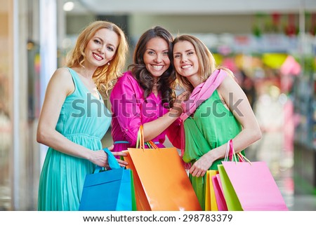 Cute girls looking at camera in the mall after shopping - stock photo