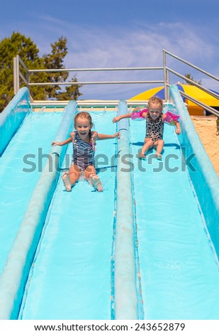 Cute girls on water slide at aquapark during summer holiday - stock photo