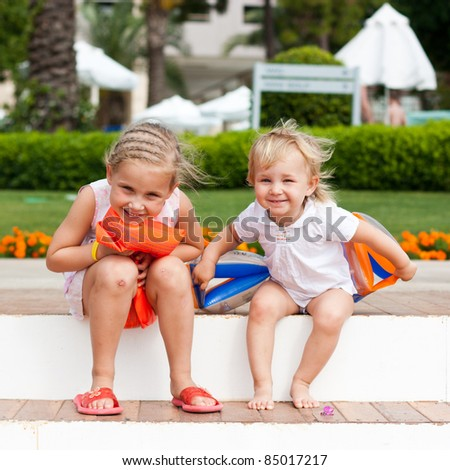 Cute girls preparing to go to swim in armbands in the resort - stock photo
