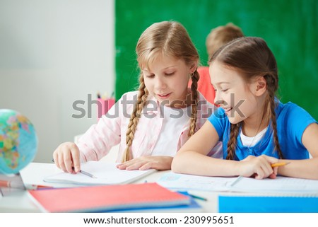 Cute girls sitting at drawing lesson and discussing ideas of picture