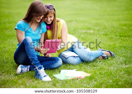 Cute girls sitting on the lawn and using the tablet computer - stock photo