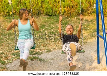 cute girls swinging - stock photo