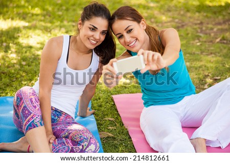 Cute girls taking a selfie with their phone while they do some yoga at a park - stock photo