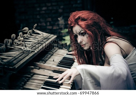 cute gothic girl plays on piano - stock photo