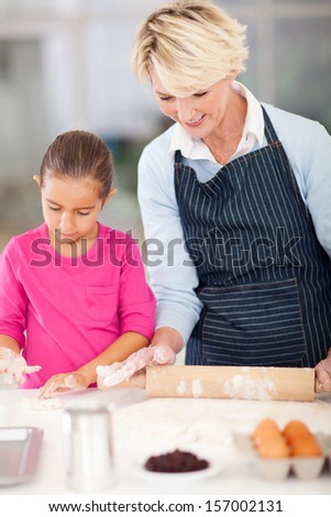 cute grandmother and granddaughter making cookies in kitchen - stock photo
