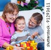 Cute Grandmother and her two grandchildren watching Christmas gifts - stock photo