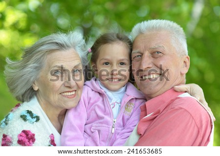 Cute grandparents smiling with granddaughter at nature - stock photo