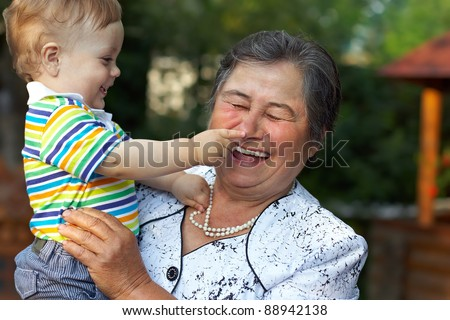 cute grandson grabbing the nose of laughing great grandmother. funny outdoors - stock photo