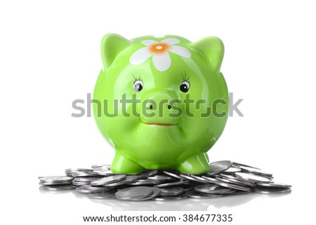 cute green piggy Bank with painted flower stands on a pile of silver coins isolated on white background
