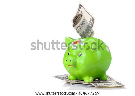 cute green piggy Bank with painted flower stands on a pile  paper banknotes isolated on white background