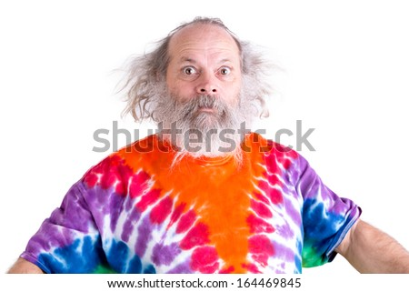 Cute grey long hair and beard senior man so surprised that his eyes came out, he is wearing a tie dye colorful T-shirt - stock photo