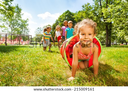Cute group of kids play crawling in tube - stock photo