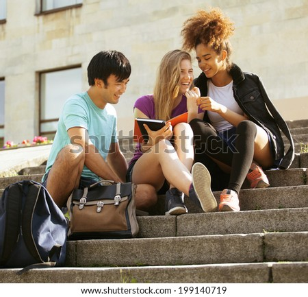 cute group of teenages at the building of university with books huggings - stock photo
