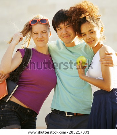 cute group of teenages at the building of university with books huggings, diversity nations, back to school - stock photo