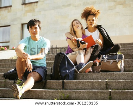 cute group of teenages at the building of university with books huggings, smiling, back to school - stock photo
