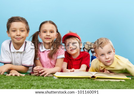 Cute guys and girl studying outside and looking at camera with a smile - stock photo