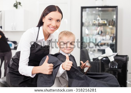 Cute hairdresser is making a haircut for child. The boy is sitting and holding a tablet. The woman and child are giving thumbs up. They are smiling and looking forward happily - stock photo