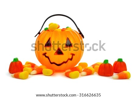 Cute Halloween Jack o Lantern candy collector with scattered candy pumpkins and candy corn over white - stock photo