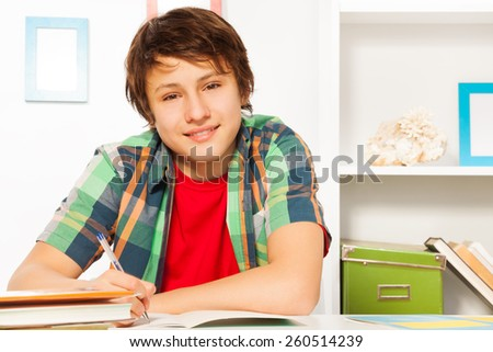 Cute handsome boy write in textbook and smile - stock photo