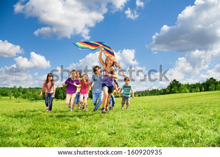 Cute happy active kids boys and girls run with kite in the park and having fun - stock photo