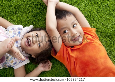 Cute happy asian siblings lying on the green grass shot at meadow