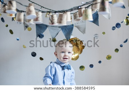 Cute happy  baby  boy wearing  blue shirt with denim bow tie on his birthday party. - stock photo