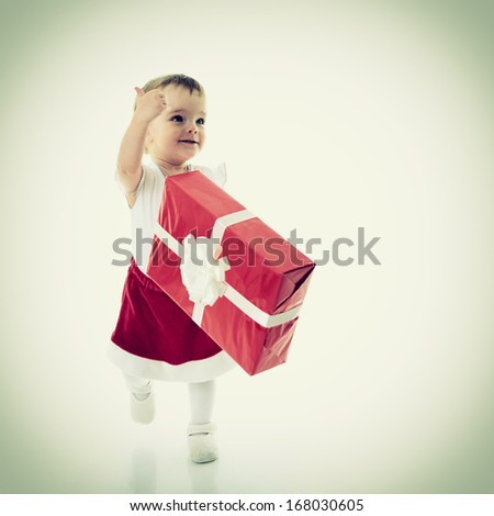 Cute happy baby girl walking and holding a present with thumb up, holidays, christmas, birthday, new year, x-mas concept - cheerful beautiful child girl with gift boxes  - stock photo