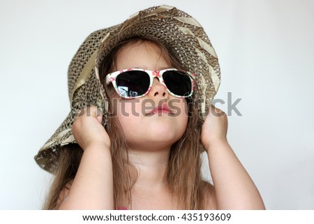 Cute happy baby girl wearing swimming suit, sun glasses and hat over white background, summer vacation concept - stock photo