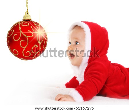 Cute happy baby in red Christmas clothes looking at sparkling red bauble decoration isolated on white - stock photo