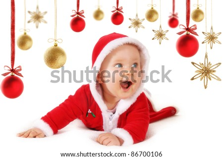 Cute happy baby in red Christmas clothes with hanging baubles and stars decorations isolated on white