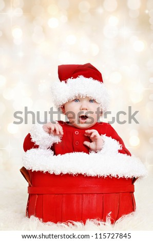 Cute happy baby in red Christmas Santa clothes sitting in a basket on defocused lights background - stock photo