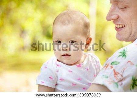 Cute happy baby laughing with his father  having fun outdoors in spring park against natural green background. family shot  - stock photo