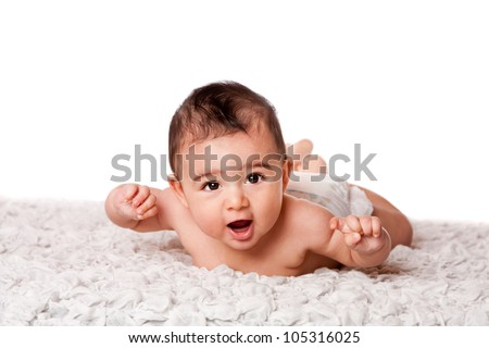 Cute happy baby laying on belly on soft surface wearing diaper, looking at camera, isolated.