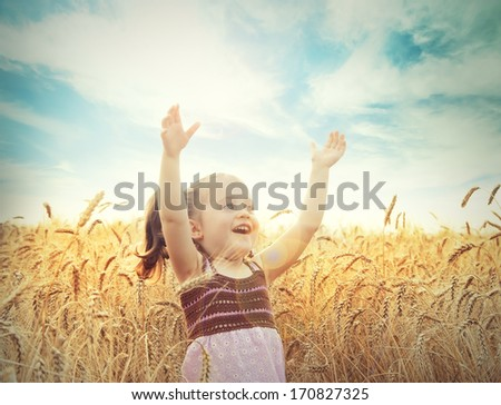 Cute happy baby playing on wheat field - stock photo
