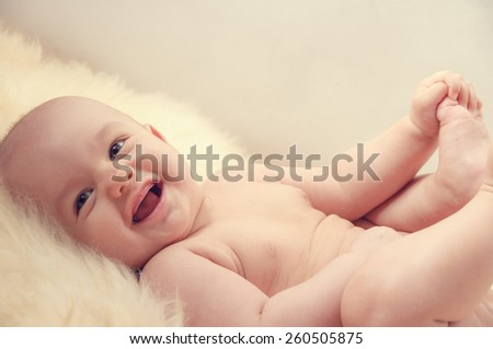 cute happy baby portrait lying on fur  - stock photo