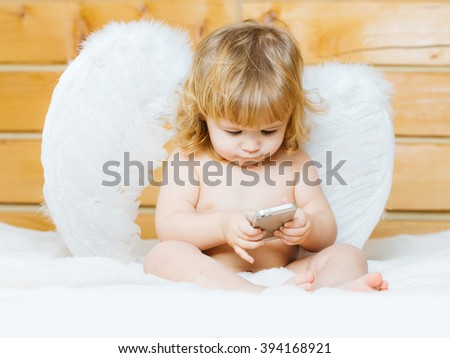 Cute happy beautiful playful child boy with wet hair sitting in hothouse bath white fluffy towel naked indoor on wooden background in feathered angel wings playing on mobile phone, horizontal picture - stock photo