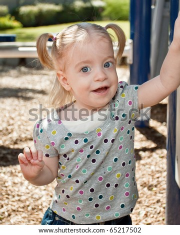 Cute happy blond toddler girl at playground - stock photo