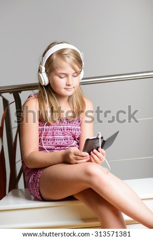Cute happy blonde girl listening to music on headphones - stock photo