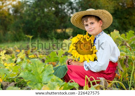 Cute happy boy hold sunflower in a summer garden - stock photo