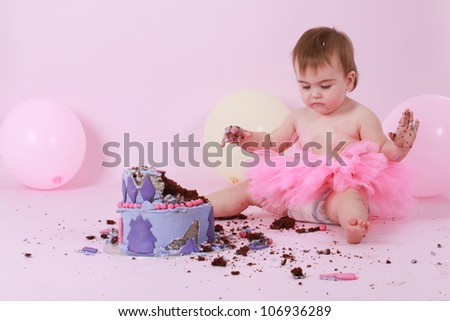 Cute happy brunette baby girl in pink tutu sitting on pink background by her birthday double tier pink and purple butter iced chocolate cake with dirty sticky hands looking at her destroyed mess - stock photo