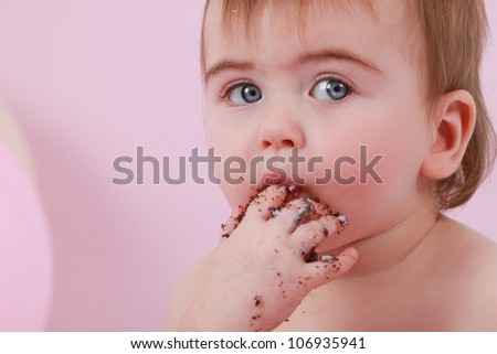 Cute happy brunette baby girl with blue eyes is tasting the chocolate cake and purple butter icing on her sticky fingers from her first birthday cake smash while sitting on a pink background sucking