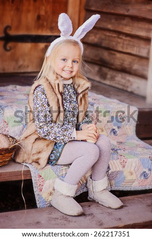 cute happy child girl wearing bunny ears for easter sitting at country house - stock photo