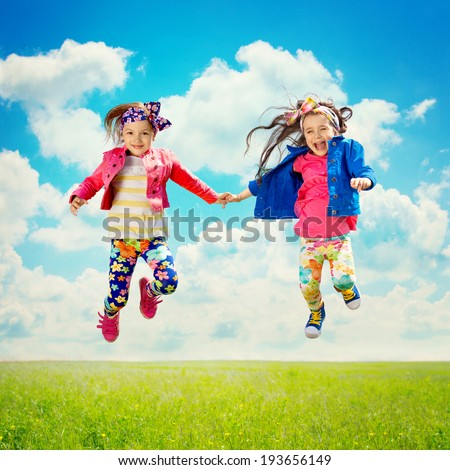 Cute happy children jumping on the spring field. Happiness, friendship, fashionable concept. - stock photo