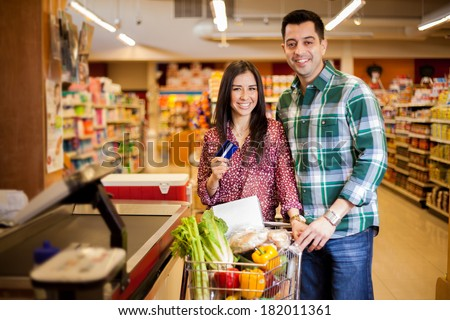 Cute happy couple paying for their food at the checkout counter with a credit card - stock photo