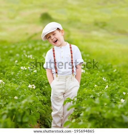 cute happy farmer boy standing in potatoes rows - stock photo