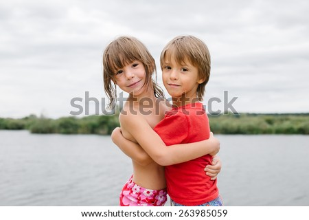 Cute happy fraternal twins enjoying their time at the beach. Brother and sister hugging. Having fun during summer vacation. Beautiful day with family at the lake - stock photo
