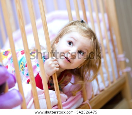 Cute happy girl jumping on the bed at home - stock photo