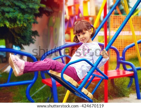 cute happy girl, kid having fun on swings at playground - stock photo
