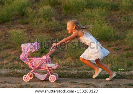 Cute happy girl playing with toy baby carriage on beautiful spring day. - stock photo